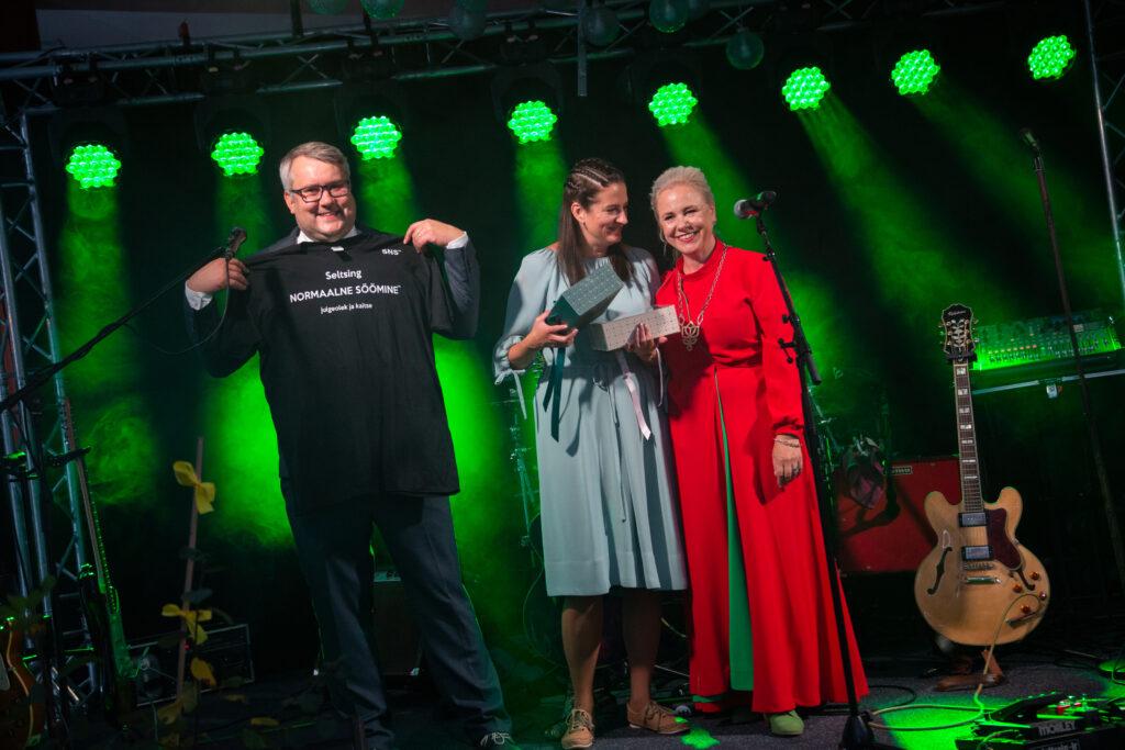 Anu Hellenurme (paremal) kinkis põllumajandus-kaubanduskoja 25. sünnipäeval koja juhatuse liikmetele särgid, mis tuletavad meelde, et hea söök on oluline mitmes mõttes. Oma särki näitab koja juhatuse esimees Roomet Sõrmus, keskel juhatuse liige Meeli Lindsaar oma särgikarbiga. Foto: Sten Semjonov